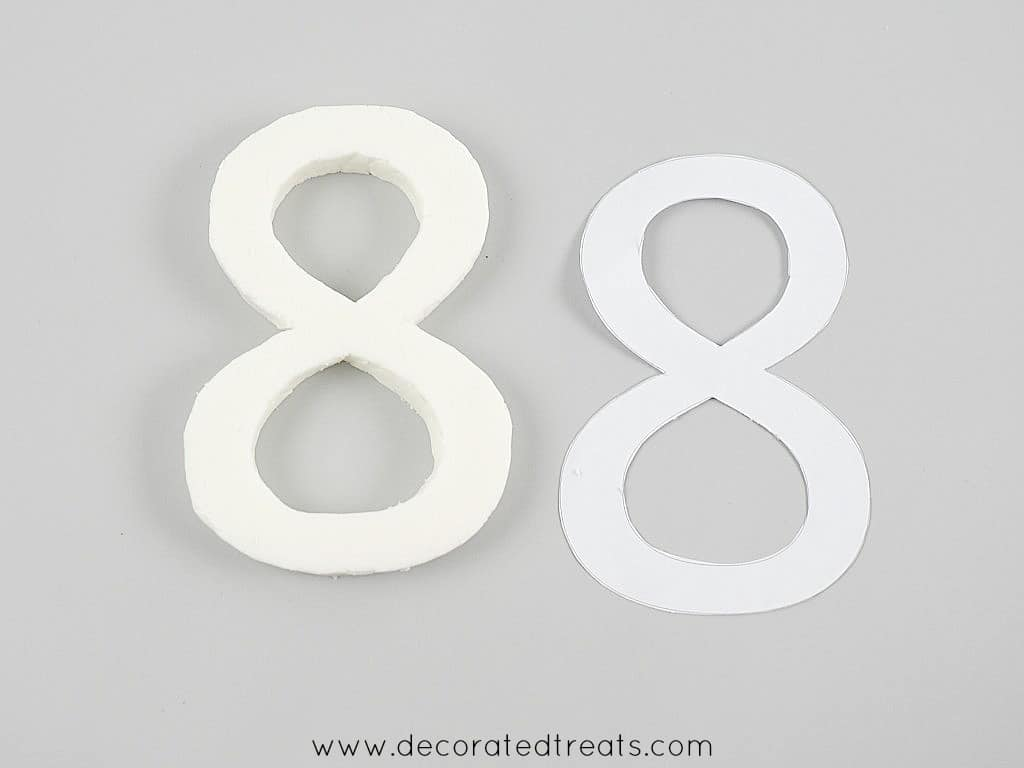 A number 8 fondant cut out and a paper template next to it