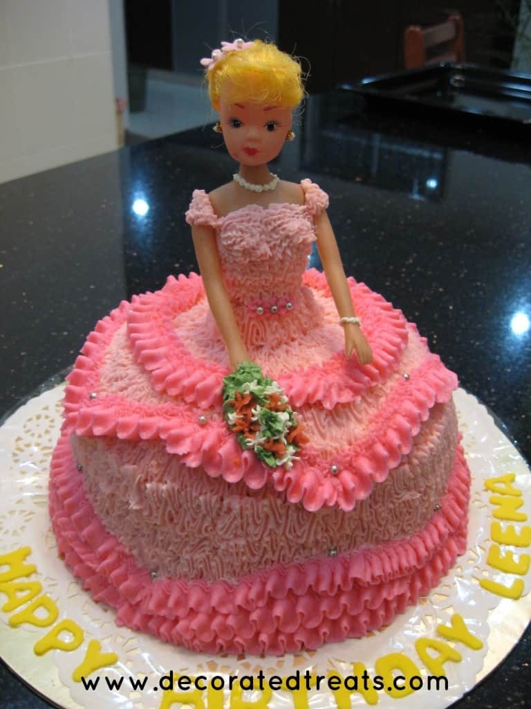 Doll cake in pink buttercream gown, with the doll holding a bouquet of buttercream flowers