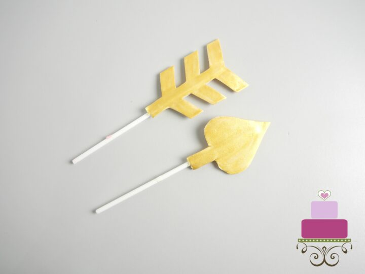 Gold painted gum paste arrow attached to white lollipop sticks.