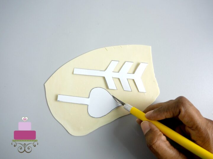 Using a sugar craft knife to cut out gum paste arrow with paper templates as guide