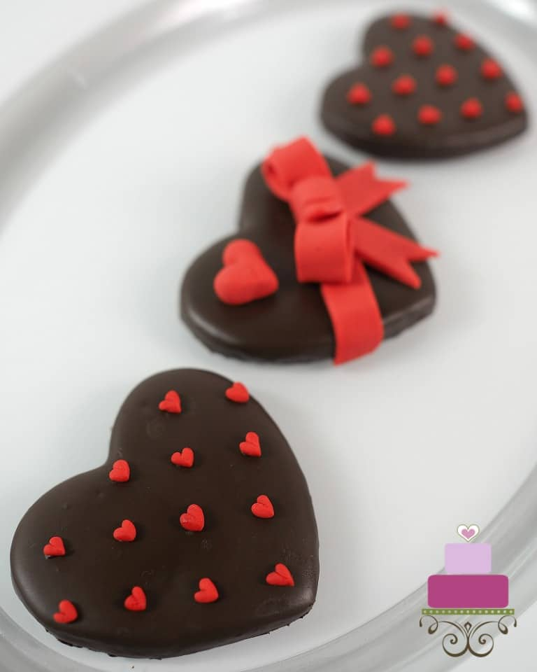 3 heart sshaped cookies covered in chocolate and decorated with red hearts and bow