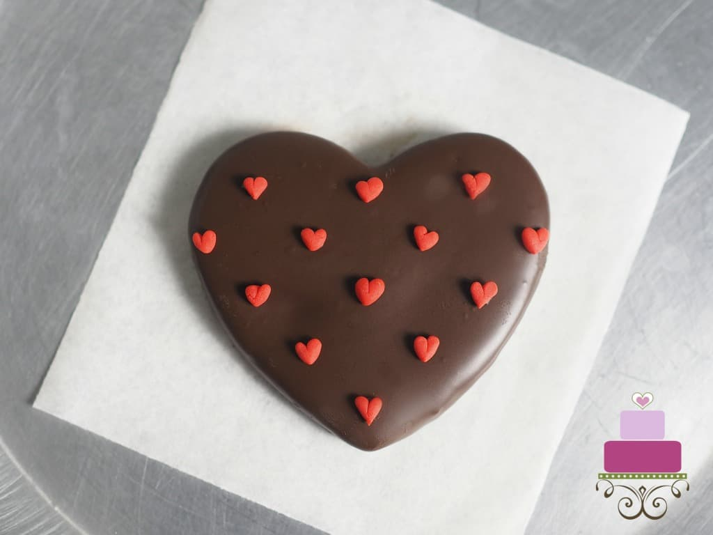 A heart shaped cookie covered in chocolate and decorated with tiny fondant hearts
