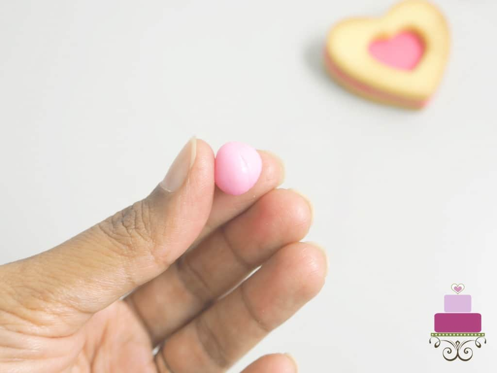 Holding a round pink fondant ball in hand