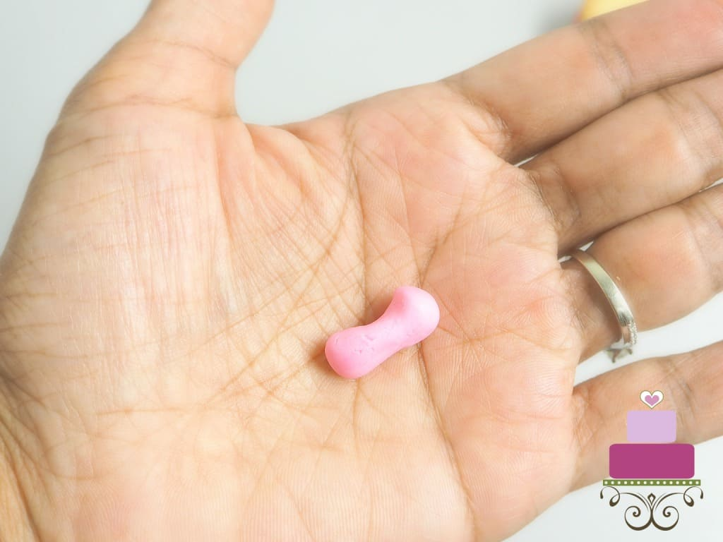 A sausage shaped pink fondant in the palm