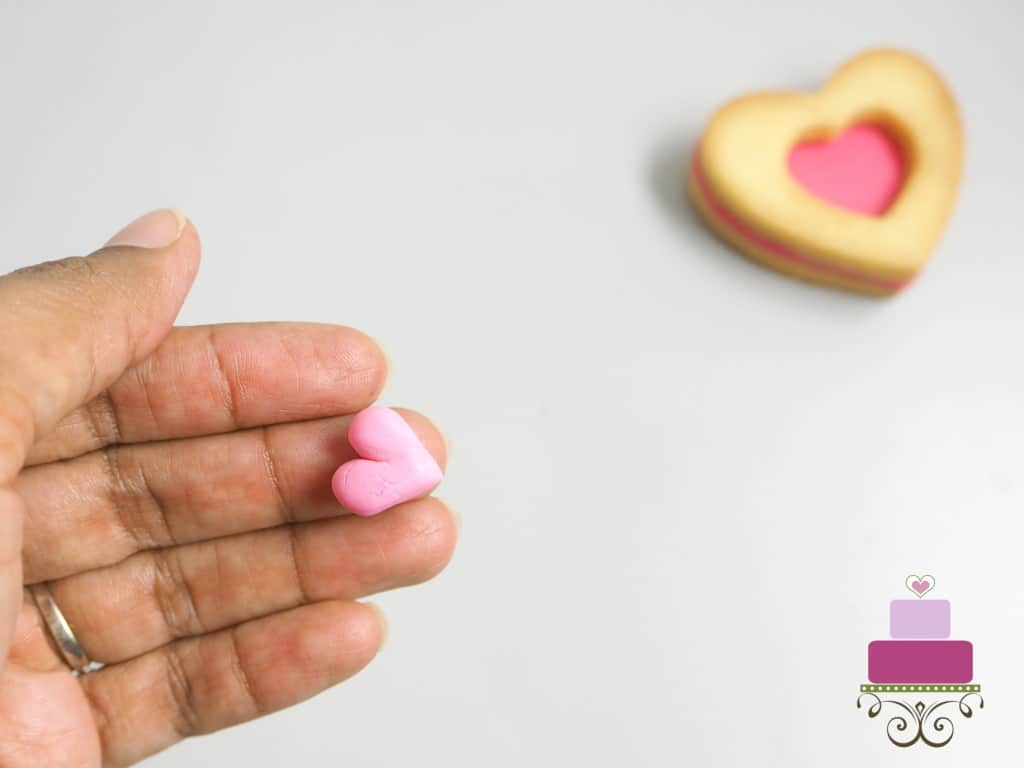 Holding small pink fondant heart in hand