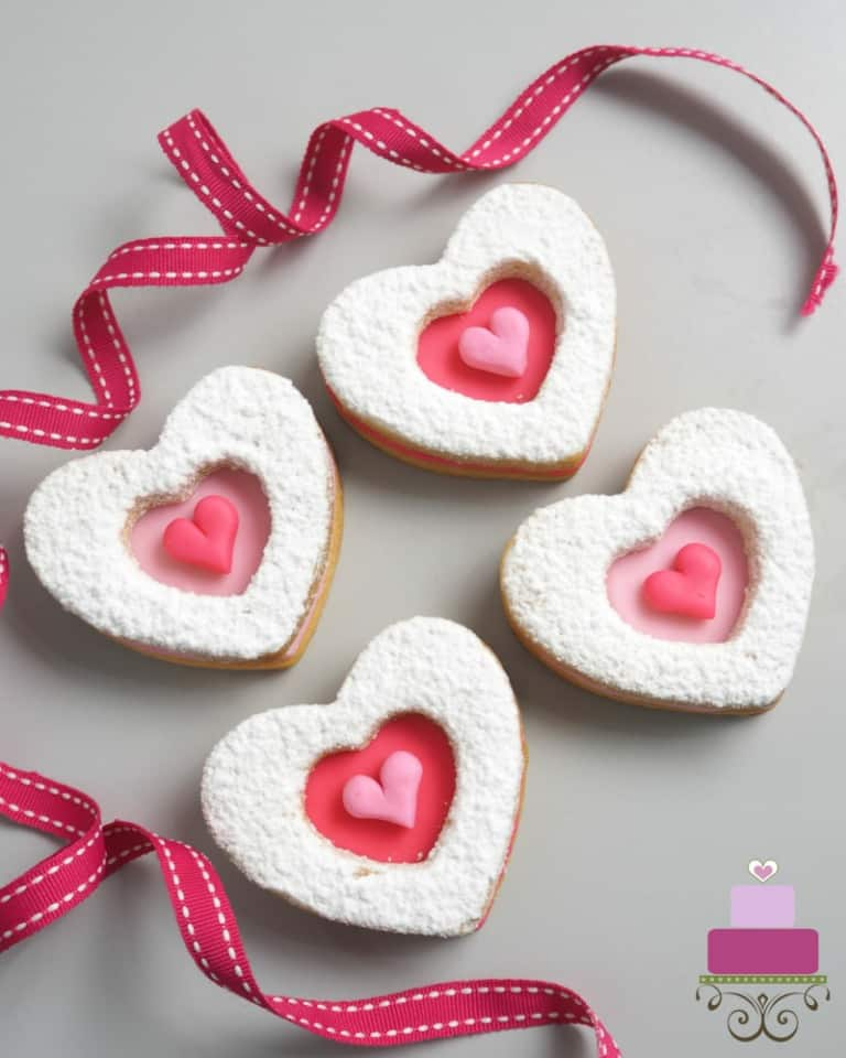 4 heart shaped cookies decorated in pink hearts and icing sugar