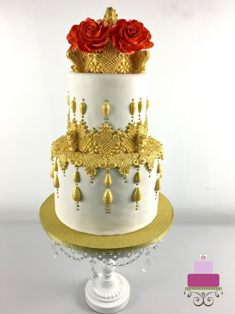 A two tier cake decorated with gold lace and red roses