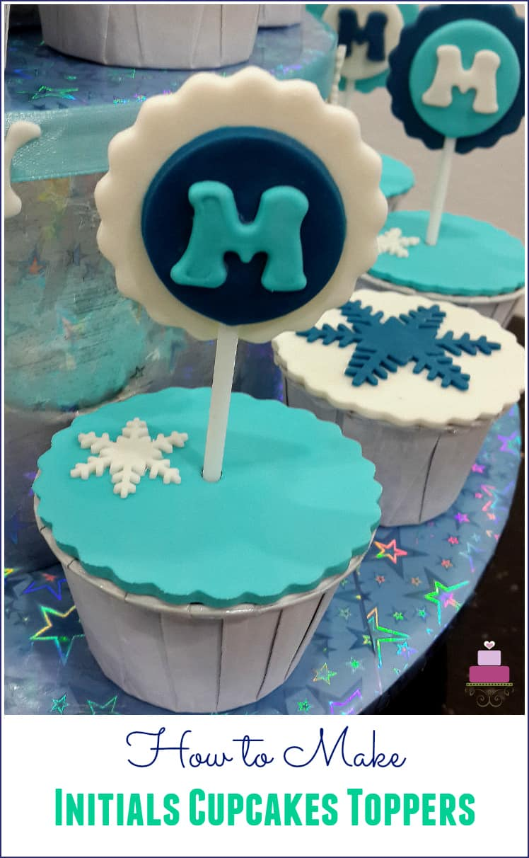 "Cupcake covered in turquoise with a letter ""m"" topper in blue, white and turquoise"