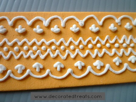 A strip of amber fondant with royal icing lace piping