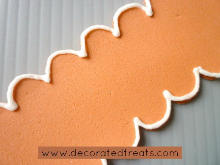 A strip of orange fondant with royal icing border piping