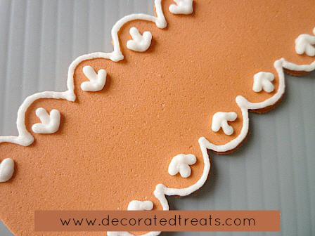 A strip of orange fondant with royal icing lace piping