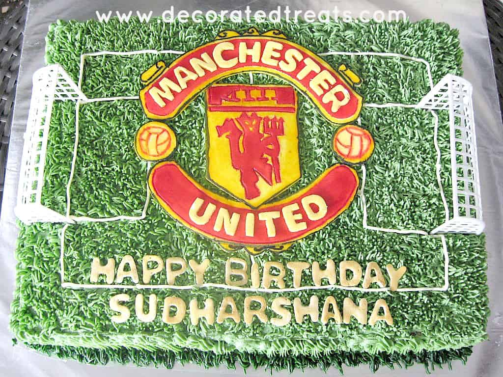 A rectangle cake decorated with green buttercream grass and a large Manchester United football club logo.