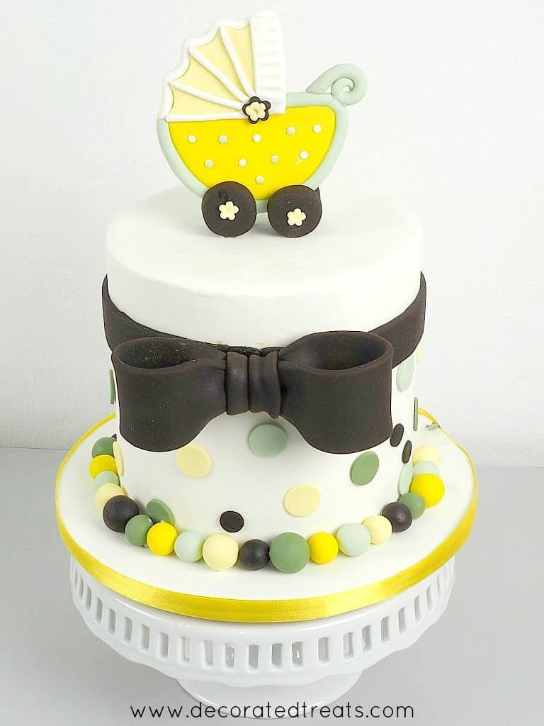 A round cake decorated with fondant bow and a baby stroller topper