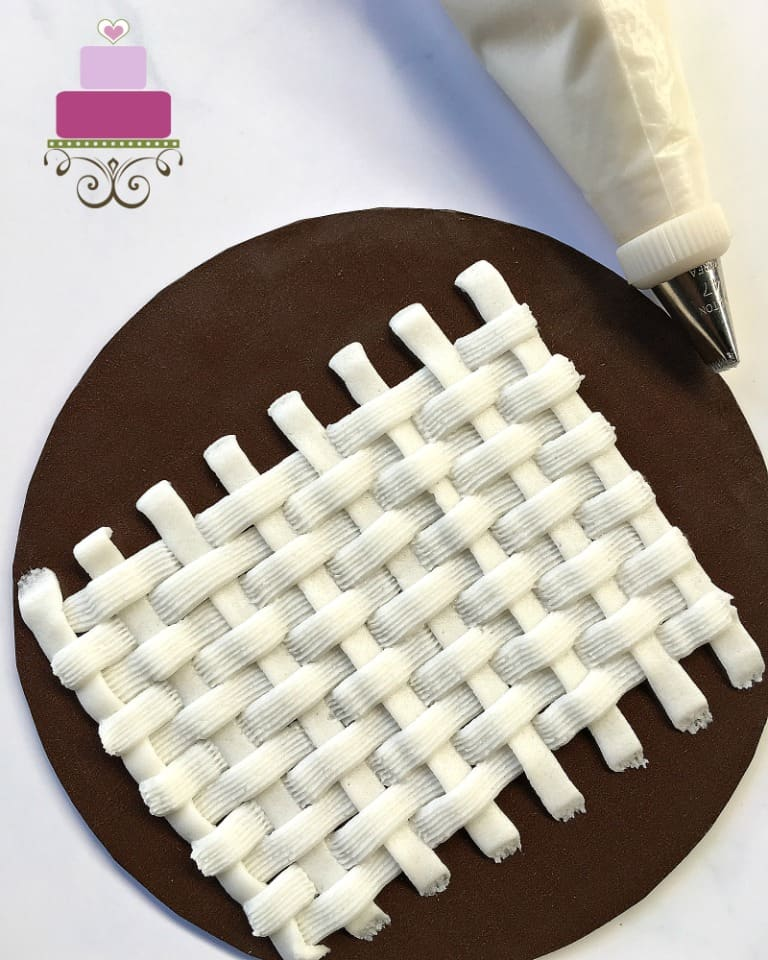 Basket weave buttercream pattern in white against brown background. In the background is a piping bag filled with white icing