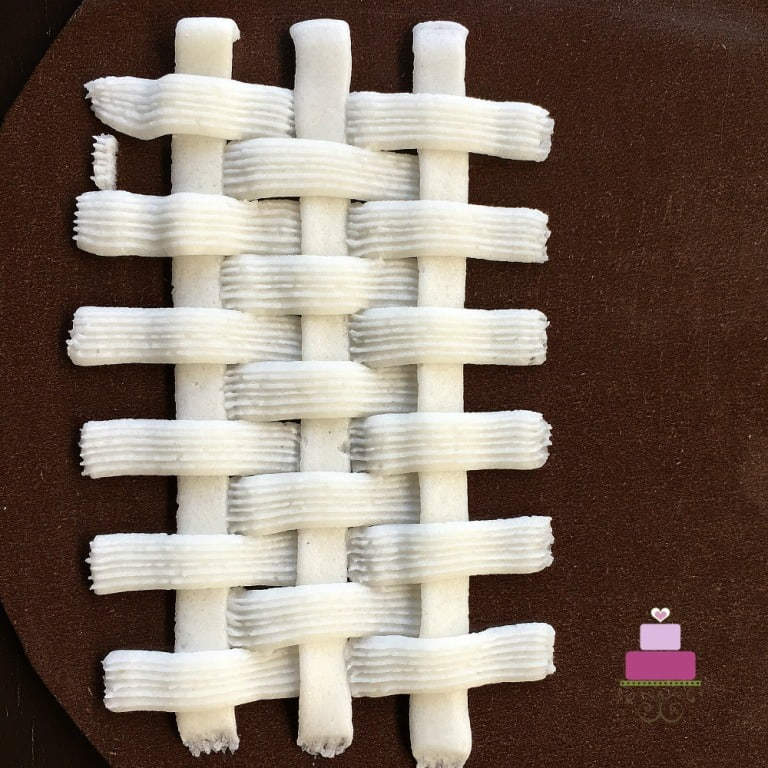 Basket weave buttercream pattern in white against brown background.