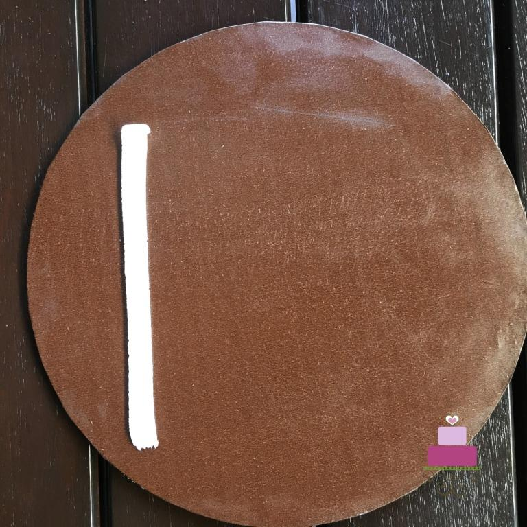 A vertical buttercream line on a brown cake board