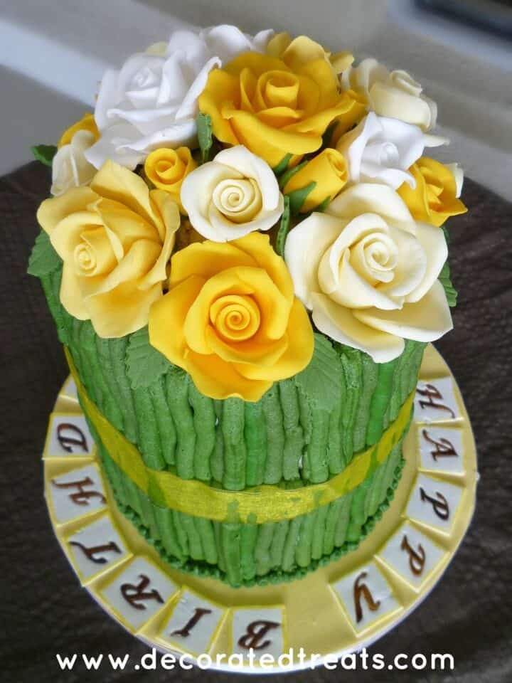 A tall cake with yellow and white roses and green sides.