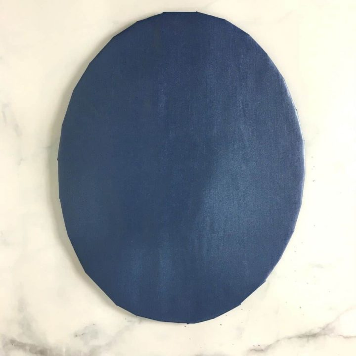 An oval cake board wrapped in blue paper
