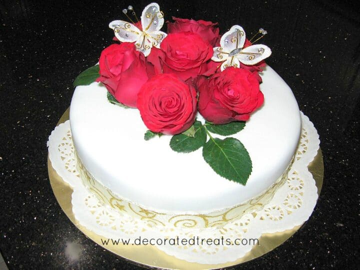 A round cake decorated with red roses and a doily covered cake board