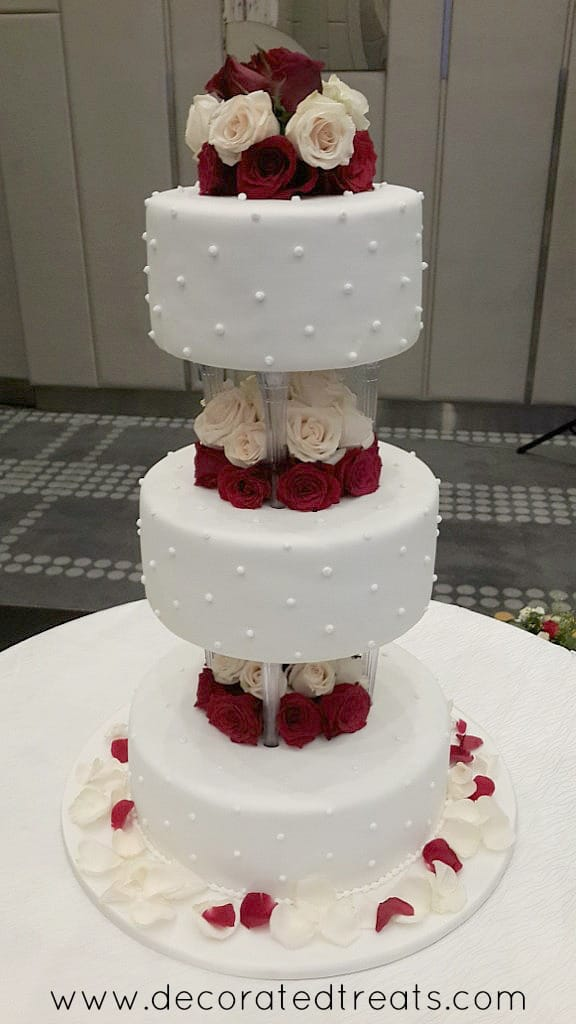 A 3 tier cake on pillars with fresh rose petals on the cake board