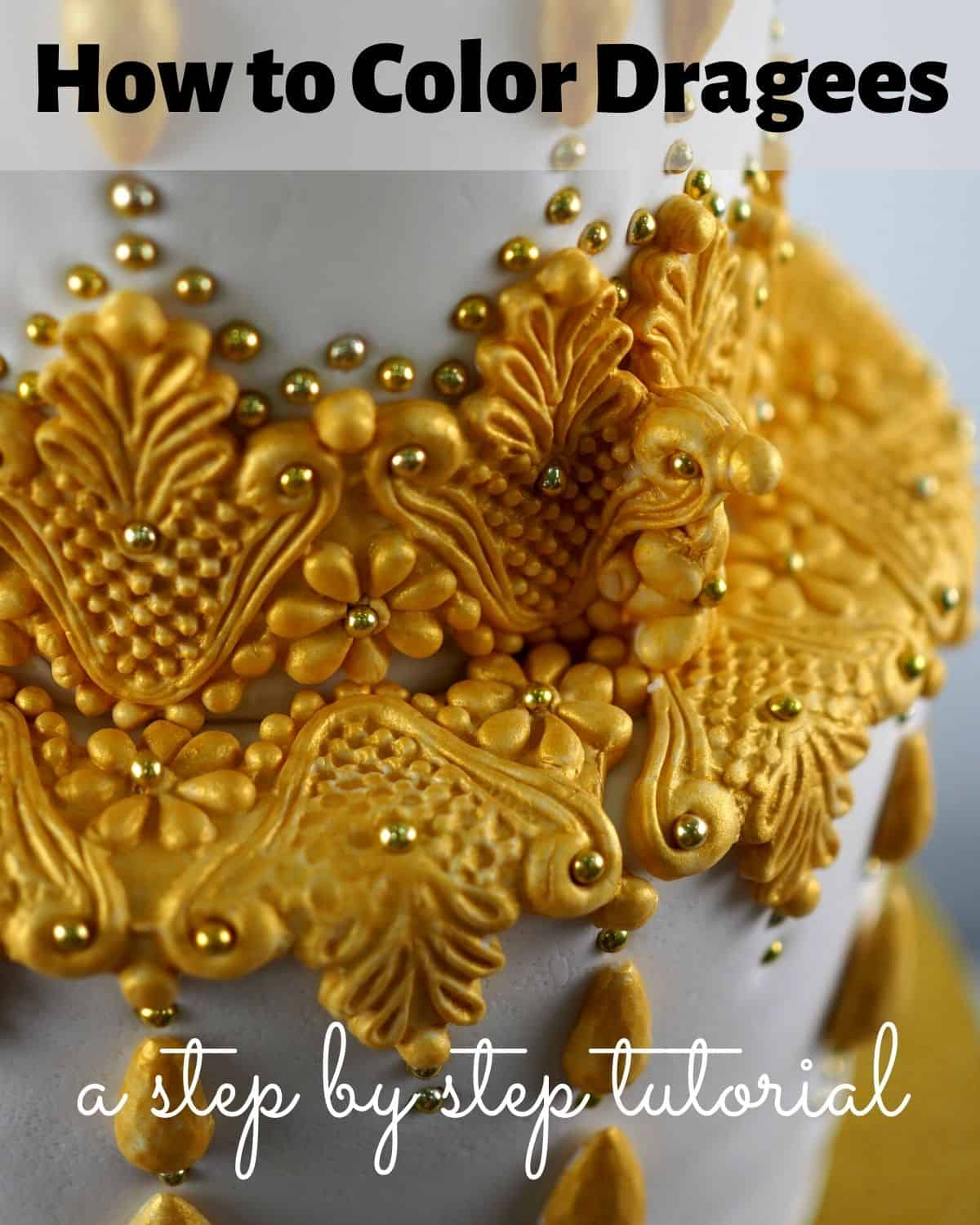A white cake decorated with gold painted molded fondant and gold dragees