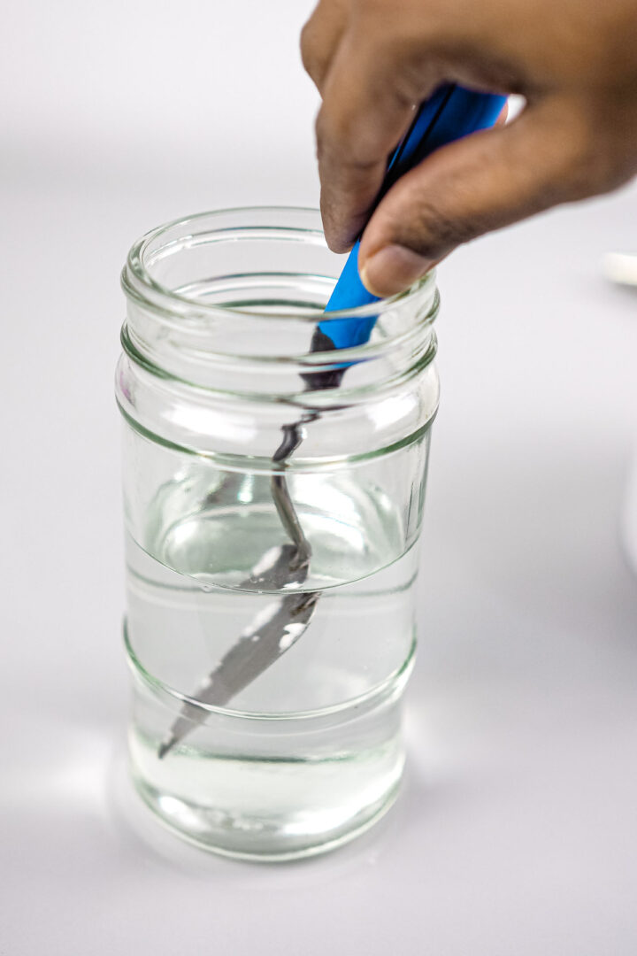 Dipping a spatula into a small jar of water