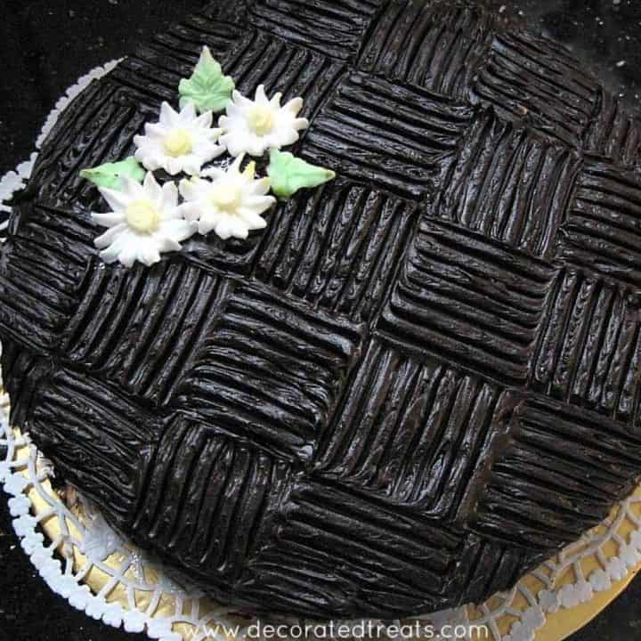 Chocolate cake with wide basket weave pattern and white royal icing daisies