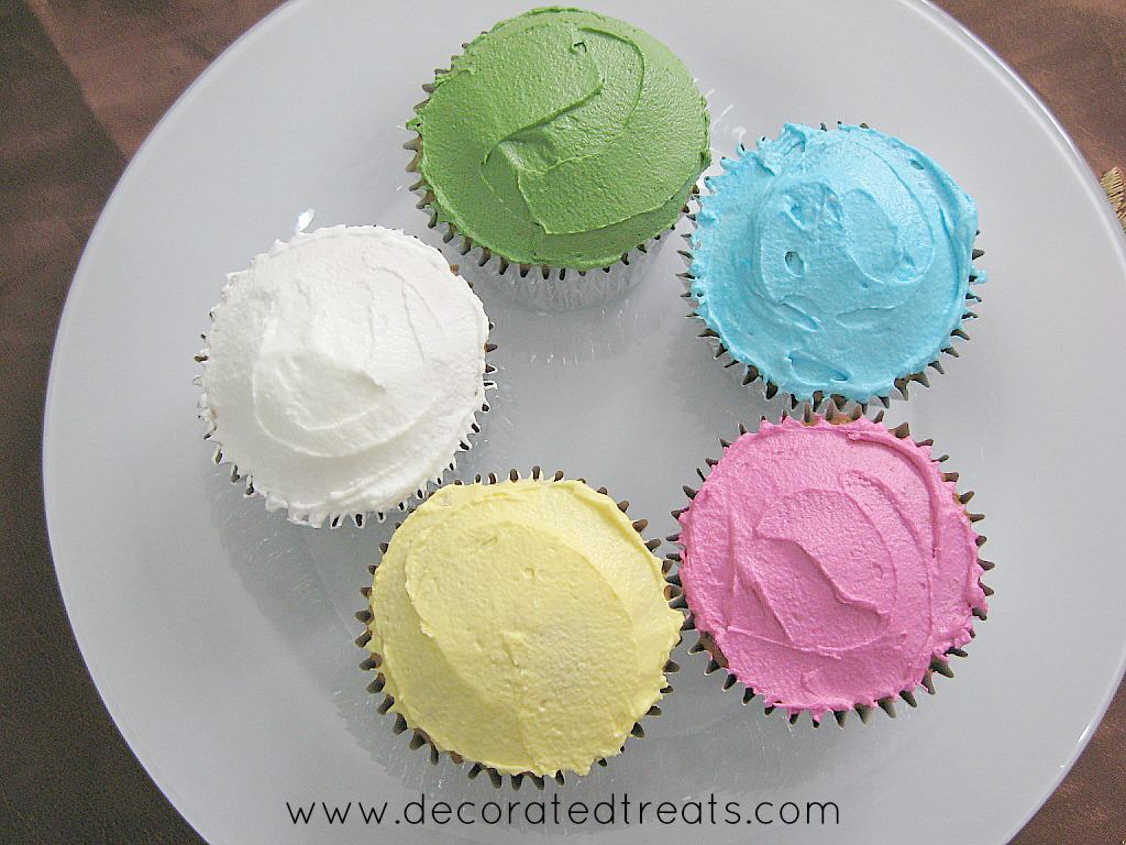 5 cupcakes on a plate. Each covered in blue, yellow, white, green and pink icing
