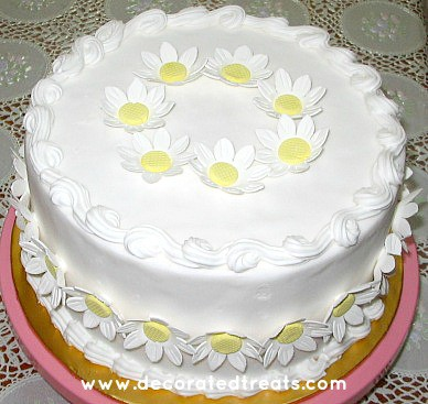 A round white cake decorated with fondant daisies
