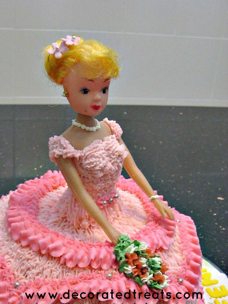 The top part of a doll cake dressed in pink buttercream