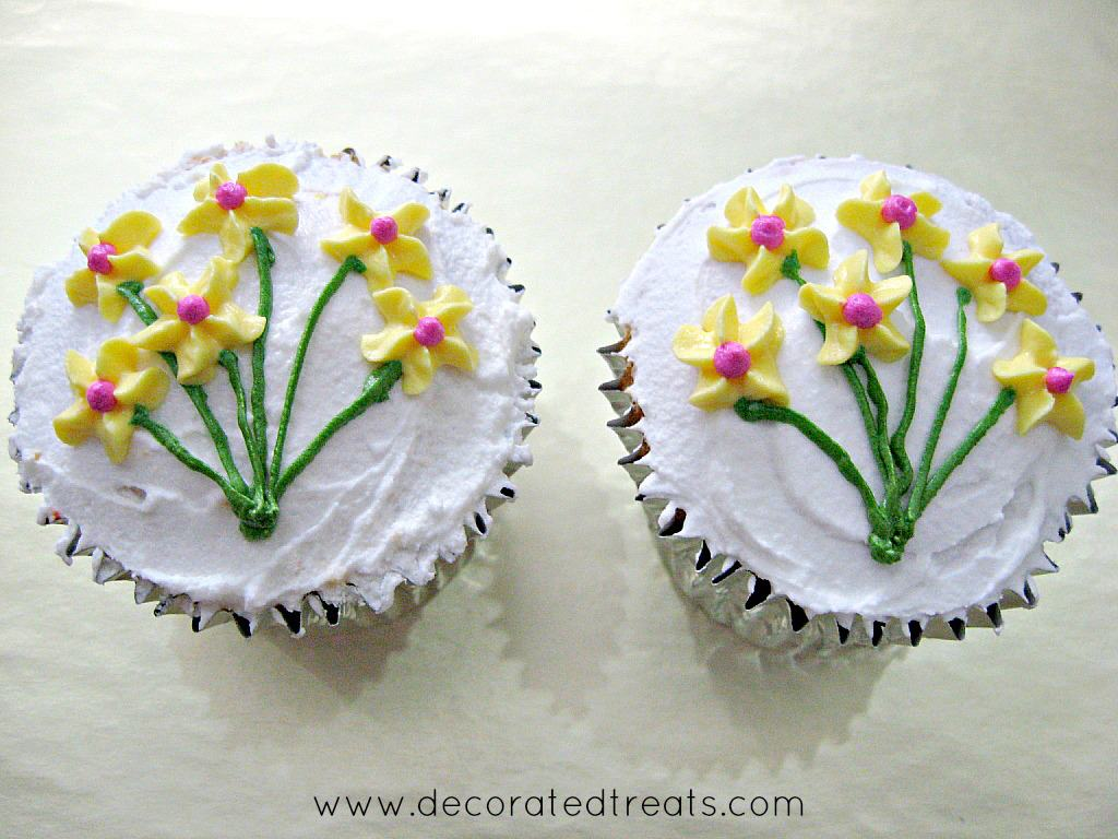 2 cupcakes covered in white icing and decorated with piped yellow flowers