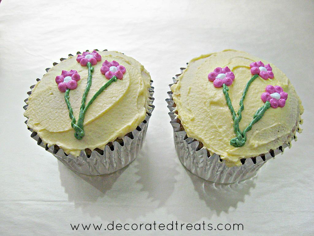 2 cupcakes covered in yellow icing and decorated with pink piped flowers