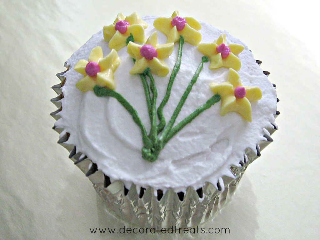 A cupcake in silver foil, covered in white icing and decorated with yellow piped flowers