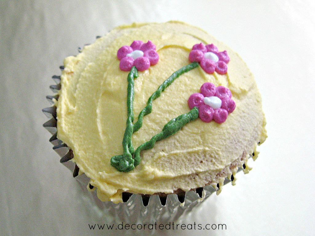 A cupcake in silver foil, covered in yellow icing and decorated with pink piped flowers