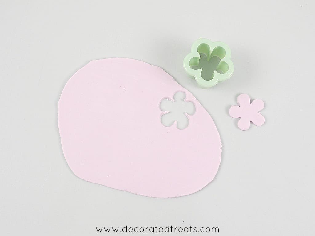 A 5 petal flower cut out of purple fondant. Next to it is the flower cutter