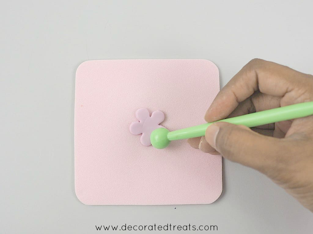Using a ball tool to thin the edges of a 5 petal, purple fondant flower on a pink sponge