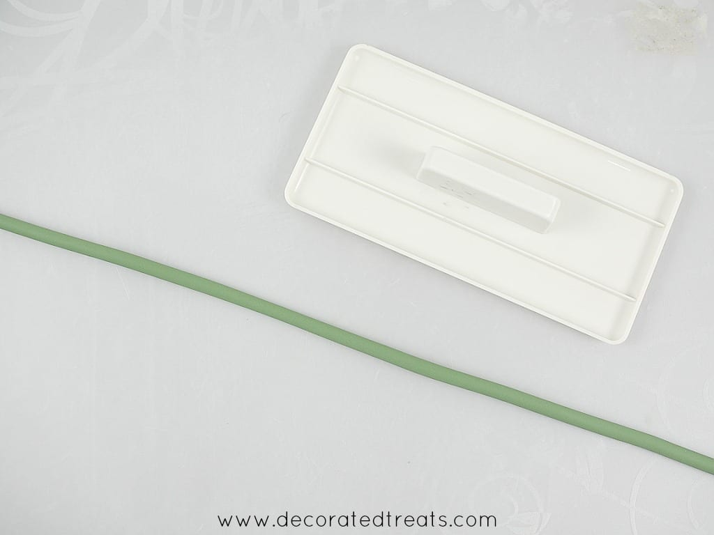 A long green strip of fondant with a fondant smoother next to it.
