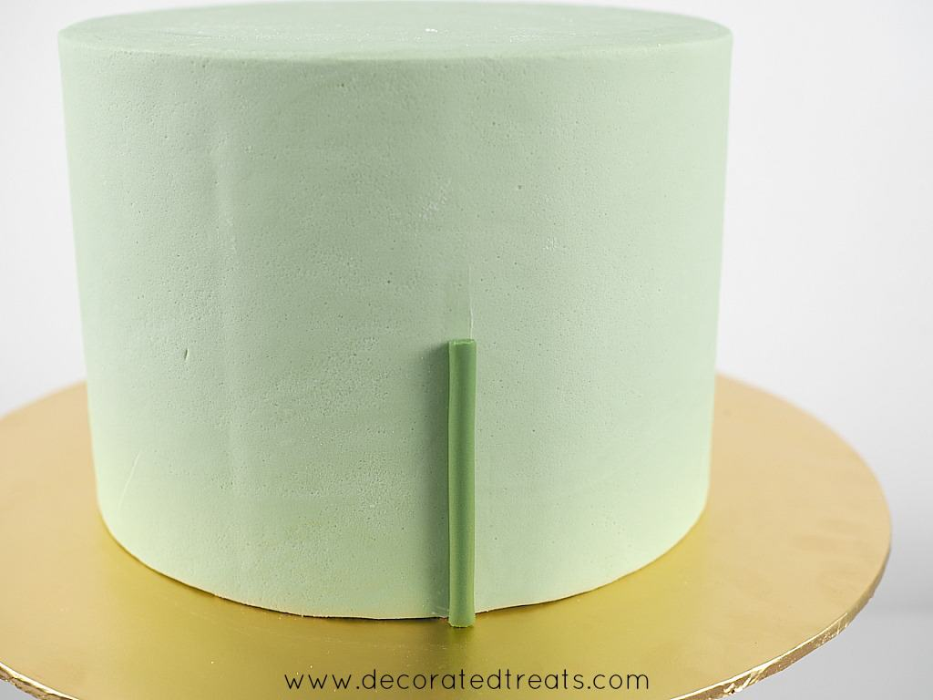 A short strip of green fondant on the sides of a cake