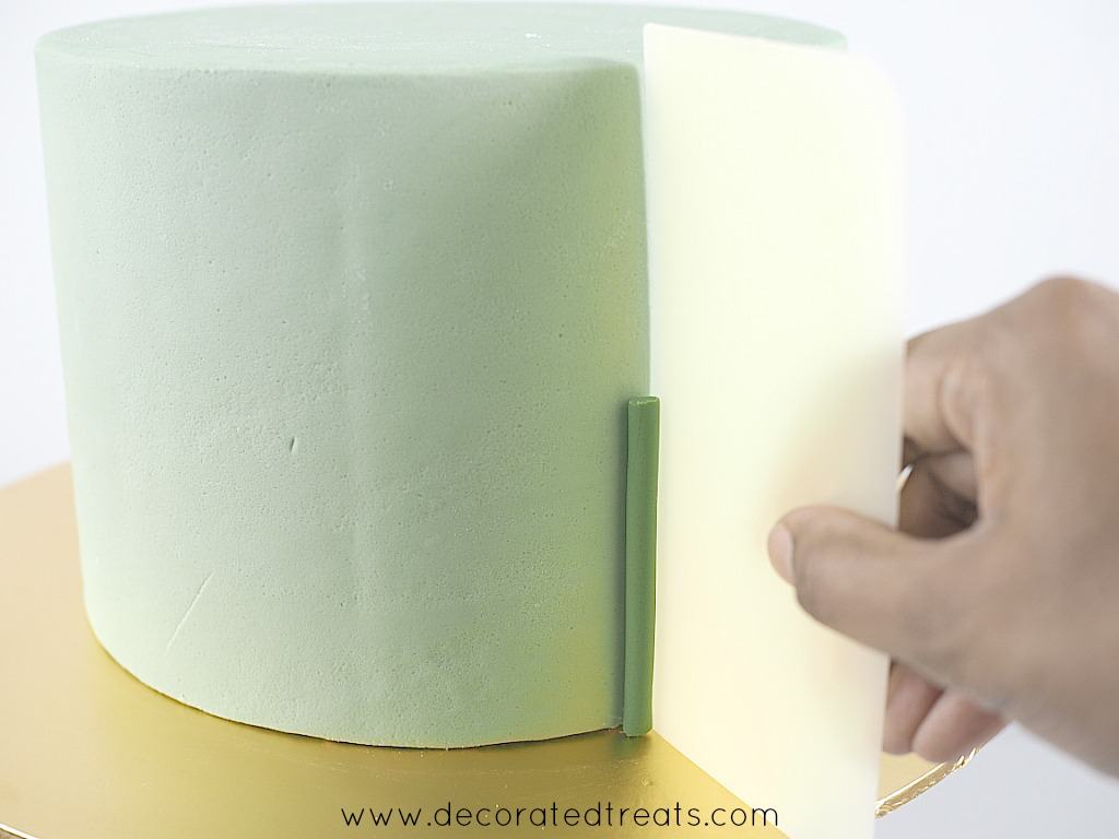 Using an icing scraper to adjust the position of a short green fondant strip on the side of a cake