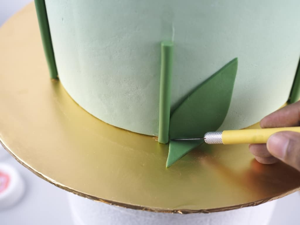 Using a sugar craft knife to cut off the excess of a fondant leave on the side of a cake