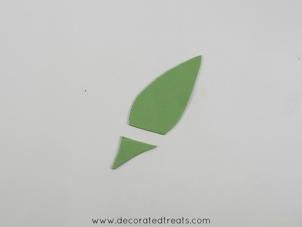 A green fondant leaf with part of it sliced off.