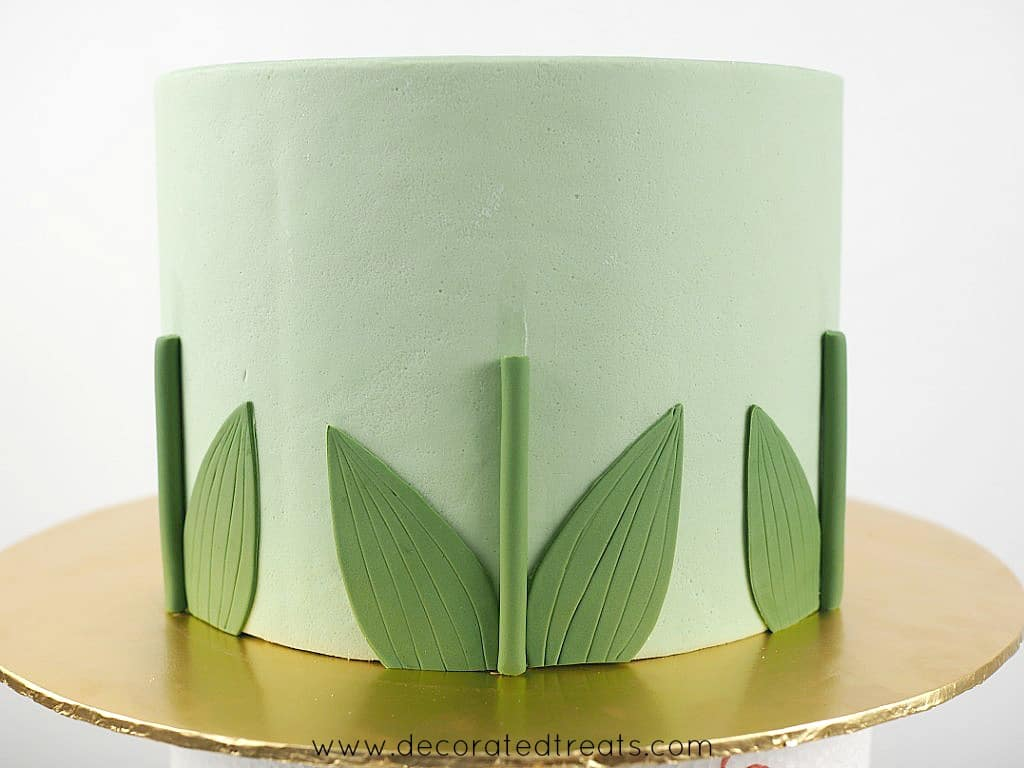 Green fondant leafs and stems on the sides of a cake