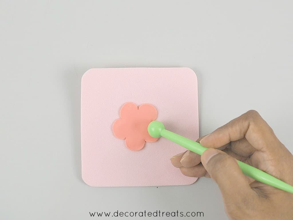 Using a ball tool to thin the edges of a 5 petal, pink fondant flower on a pink sponge