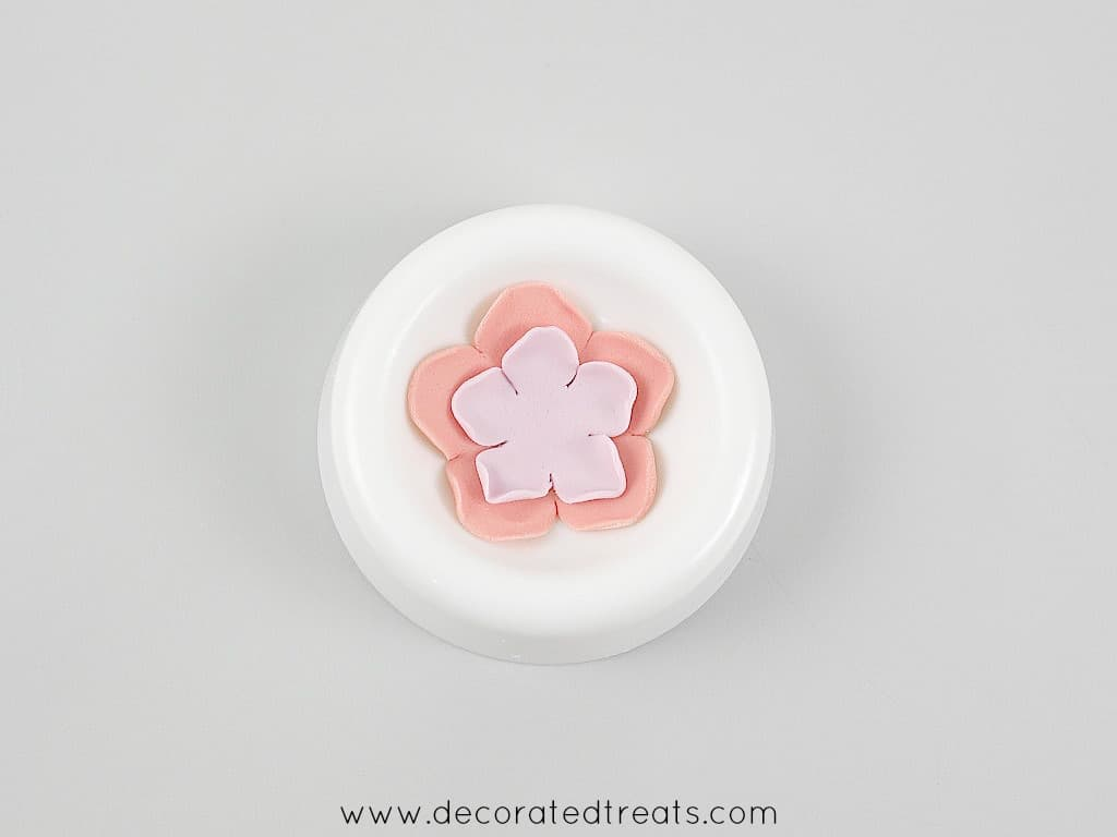 A pink and purple 5 petal fondant flower in a flower former