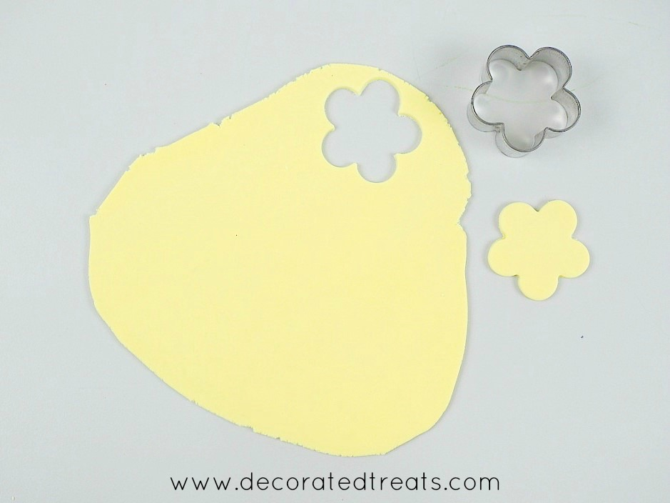 A piece of yellow rolled fondant with a flower cut out of it using a 5 petal flower cutter. Cutter and the cut out are in the background