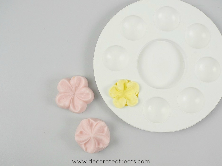 A yellow 5 petal flower in a flower former. On the side are pink silicone molds