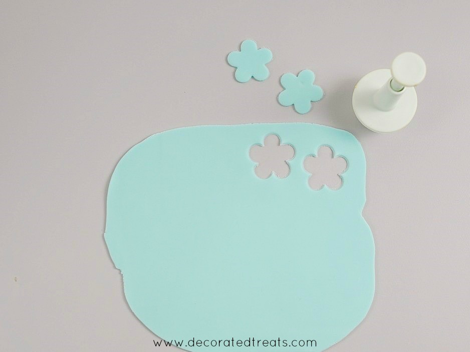 A piece of blue rolled fondant with 2 flowers cut out of it using a 5 petal flower plunger cutter. Cutter and the cut outs are in the background