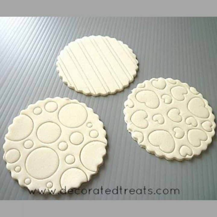 3 round fondant pieces embossed with lines, circles and heart pattern