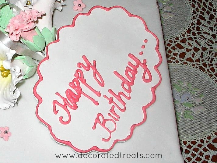 A fondant plaque with happy birthday message piped in pink