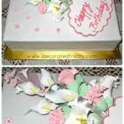 A rectangle cake with a bouquet of gum paste flowers on it and a fondant plaque